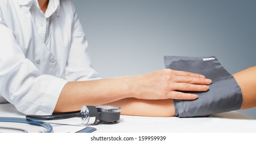 Doctor puts cuff of sphygmomanometer on the patient's arm