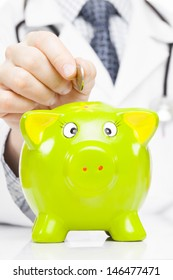 Doctor putting a coin into piggy bank as an idea for healthcare insurance and savings for medical expenses