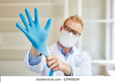 Doctor putting gloves on as labor protection