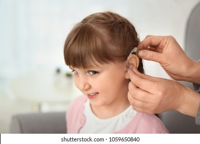 Doctor putting hearing aid in little girl's ear indoors