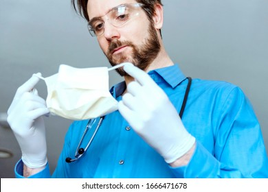 Doctor putting on respirator face mask wearing exam gloves, eye glasses and stethoscope.