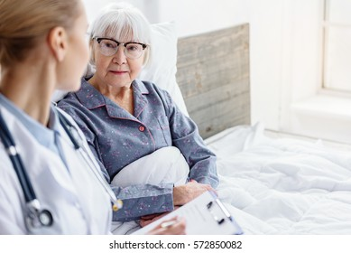 doctor questioning pensioner in hospital