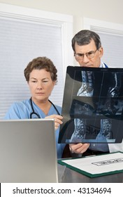 Doctor and Radiologist or Nurse reviewing and discussing patient's MRI scan and comparing with images on the laptop computer.