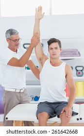 Doctor raising a young man arm in medical office