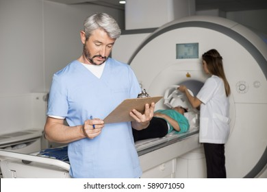 Doctor Reading Clipboard With Colleague Preparing Patient For CT