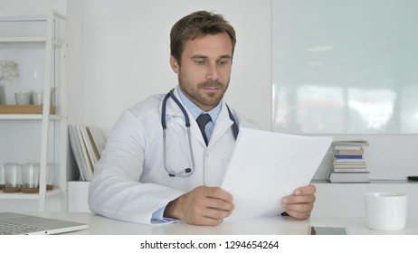 Doctor Reading Documents in Clinic, Paperwork