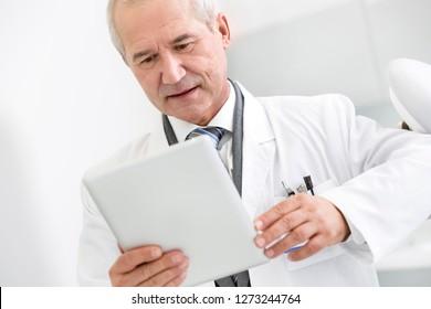 Doctor reading medical report on digital tablet at dental clinic