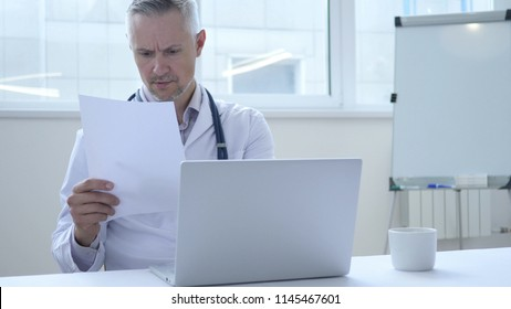 Doctor reading Medical Report of Patient in Clinic