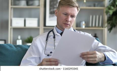 Doctor Reading Medical Report of Patiet, Paper Work