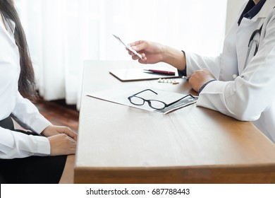 Doctor recommending medicines for her middle aged patient.