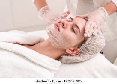 The doctor removes the gel from the patients face and apply a therapeutic cream. Anti acne phototherapy. Beautiful woman during photo rejuvenation procedure. Face skin treatment at cosmetic clinic.