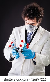 a doctor or researcher with a white lab coat holding a trinitrotoluene tnt molecular model