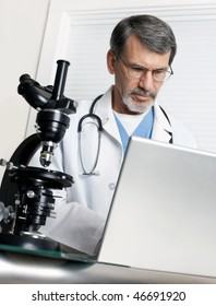 A doctor researching at the microscope and laptop computer.