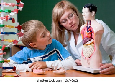 Doctor and schoolboy with dummy (human body) at anatomy class