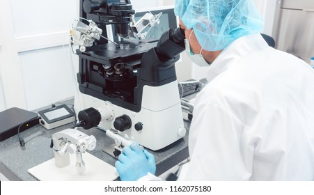 Doctor or scientist looking thru microscope in biotech lab