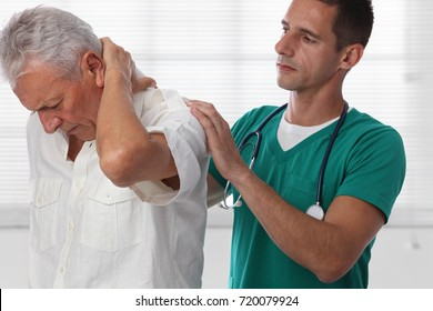 Doctor and senior male patient suffering from back pain during medical exam.