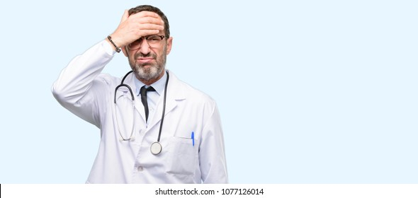Doctor senior man, medical professional terrified and nervous expressing anxiety and panic gesture, overwhelmed isolated over blue background