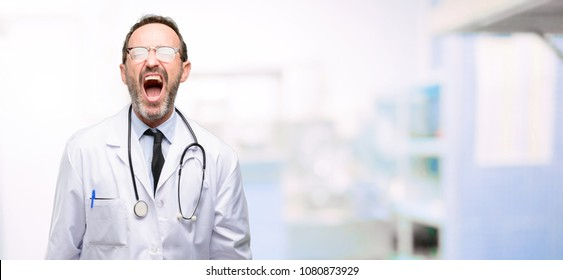 Doctor senior man, medical professional stressful, terrified in panic, shouting exasperated and frustrated. Unpleasant gesture. Annoying work drives me crazy at hospital
