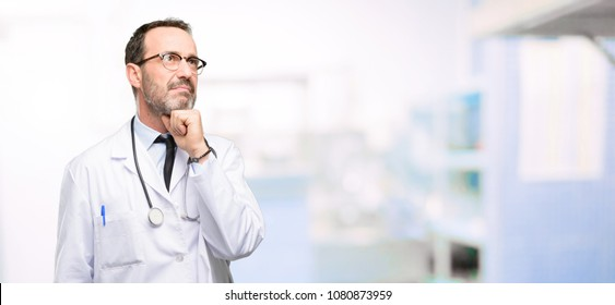 Doctor senior man, medical professional thinking and looking up expressing doubt and wonder at hospital