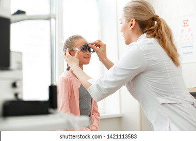 Doctor setting device. Positive good-looking child getting ready for measuring her eyeballs during appointment with ophthalmologist
