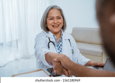 The doctor shakes hands with the patient after the examination