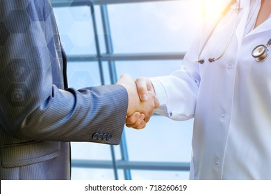 Doctor shakes hands with patient in the background of the window.