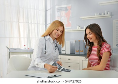 Doctor showing baby ultrasound image to pregnant woman