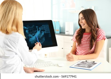 Doctor showing baby ultrasound image on computer to pregnant woman