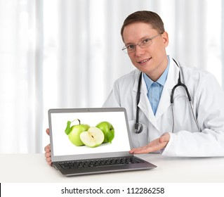 doctor showing green apples on his laptop computer