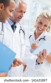 Doctor showing his tablet to his colleagues