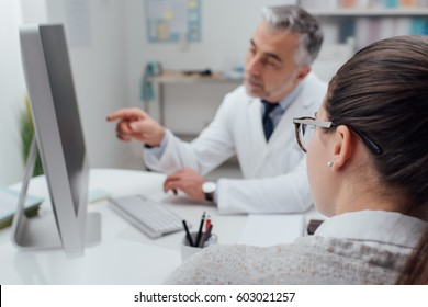 Doctor showing medical records on his computer to his patient, he is pointing at the screen