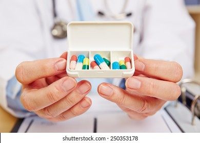 Doctor showing pill dispenser filled with medication in his hands