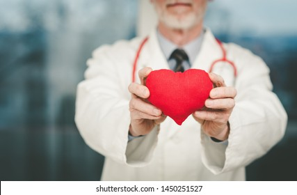 Doctor showing red heart; cardiology concept