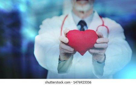 Doctor showing red heart; cardiology concept; multiple exposure