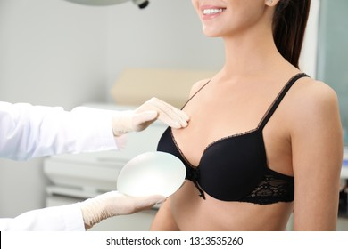 Doctor showing silicone implant for breast augmentation to patient in clinic, closeup. Cosmetic surgery