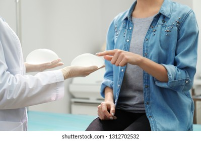 Doctor showing silicone implants for breast augmentation to patient in clinic, closeup. Cosmetic surgery