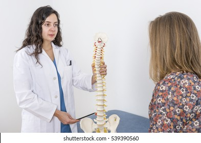 Doctor showing a skeleton to a patient. Back pain.