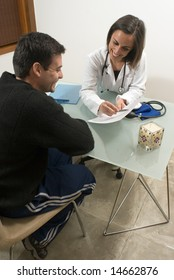 A doctor is showing some information to her patient.  They are both smiling and looking at the paper.  Vertically framed photo.
