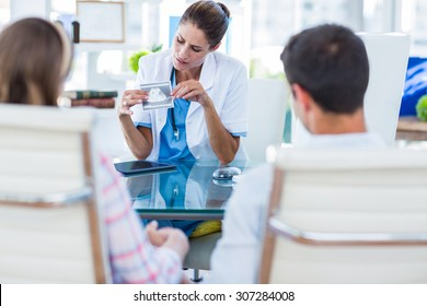 Doctor showing sonagram to couple in office at the hospital