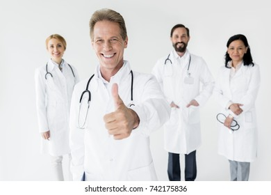 doctor showing thumb up and smiling at camera while colleagues standing behind, isolated on white