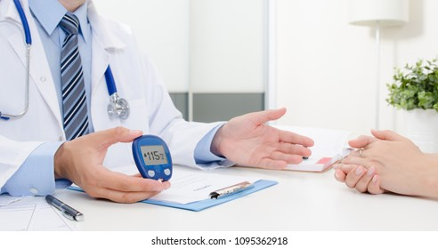 Doctor shows glucometer with glucose level. Doctor and patient diabetes consultation in office or clinic.