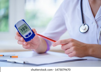 Doctor shows glucose meter with blood glucose level to diabetes patient during medical consultation and examination in clinic. Diabetic lifestyle and healthcare