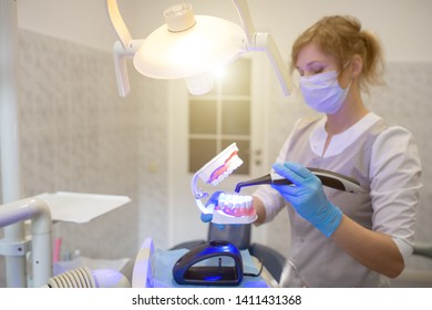 the doctor shows the jaw how to use a modern photo polymerization lamp in the dental office
