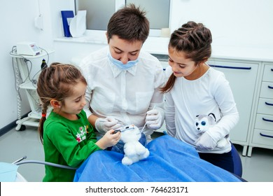 The doctor shows the little girls the procedure for the treatment of teeth. Dentist woman save atmosphere of calm and purity especially for young patients.