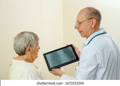 Doctor shows the results of an examination of the lungs of an elderly woman on the screen of a tablet