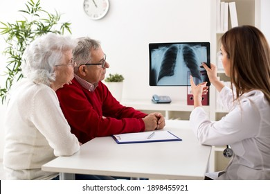 Doctor shows results to old patient x-ray of the lungs at clinic