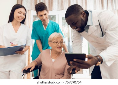 The doctor shows something on the tablet to an elderly patient in a nursing home. She is very surprised by what she saw. The doctor smiles.