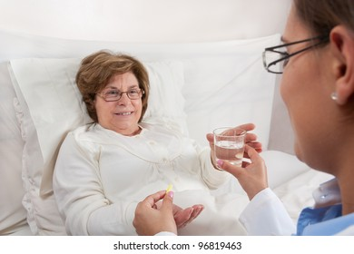 Doctor sitting in bed, gives medication and a glass of water to recovering senior patient