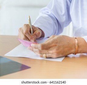 doctor sitting at desk holding pen with files short note. Healthcare concept