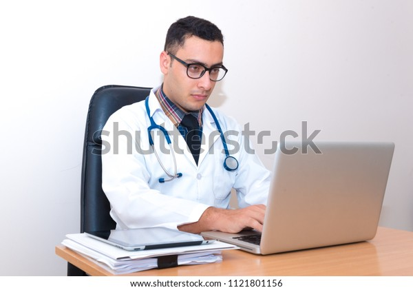 Doctor sitting at the desk, using laptop typing and searching data from the internet or searching patient record data.
